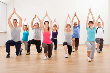 yoga class: Large diverse group of people doing aerobics exercises in a class in a gym in a health and fitness concept Stock Photo