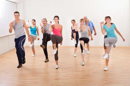 Gran grupo diverso de personas que hacen ejercicios aeróbicos en una clase en un gimnasio en un concepto de salud y bienestar