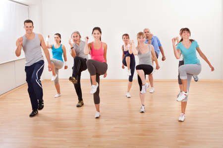 Large diverse group of people doing aerobics exercises in a class in a gym in a health and fitness concept