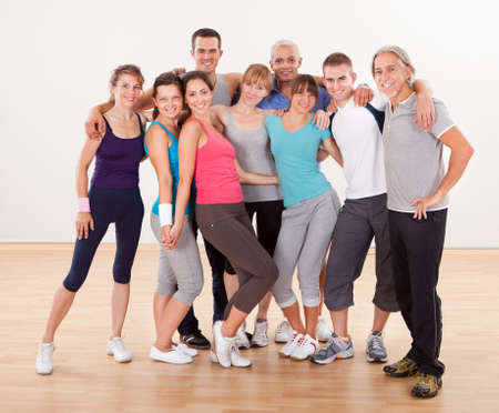aerobic training: Large group of diverse male and female friends posing together at the gym in their sportswear Stock Photo
