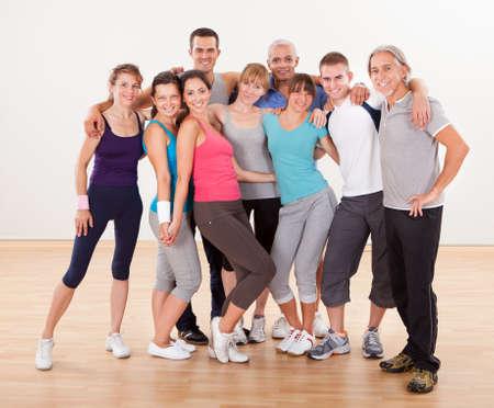 Nagy csoportja a különböző férfi és női barátok pózol együtt a tornaterem a sportruházat Stock fotó