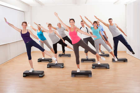 aerobics class: Diverse group of people in a class doing aerobics balancing on boards exerting control over their muscles and breathing