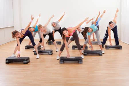 Diverse group of people in a class doing aerobics balancing on boards exerting control over their muscles and breathing photo
