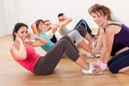 Happy group of diverse people full of health and vitality working out in a gym strengthening abdominal muscles doing head lifting Stock Photo