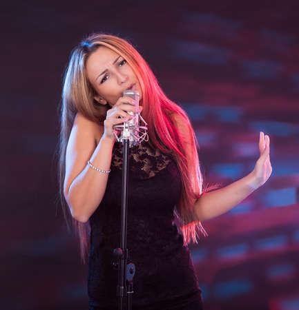 cantando: Hermosa cantante femenina con micr�fono aislados en blanco