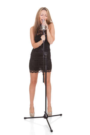 Beautiful female singer with a microphone isolated on white photo
