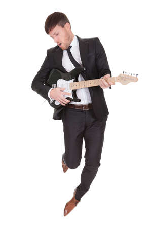 stage performer: Elegant young man jumps while playing electric guitar