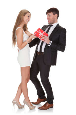 sexy couple embrace: Girl in high shoes holds wrapped gift given by boyfriend.