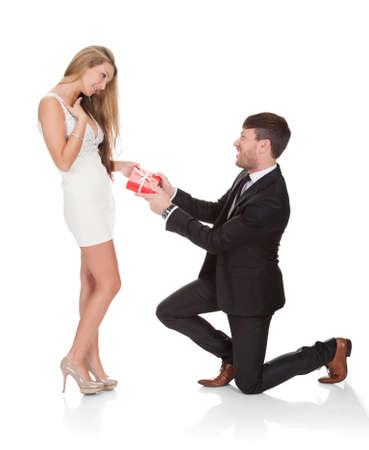 mujer arrodillada: Inteligente chico se arrodilló sobre sus rodillas luego le da regalo a la esposa. Foto de archivo