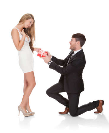 kneeling man: Smart guy kneeled on his knees then gives gift to wife. Stock Photo