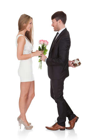 giving back: Man giving fresh flowers to woman. Isolated on white Stock Photo