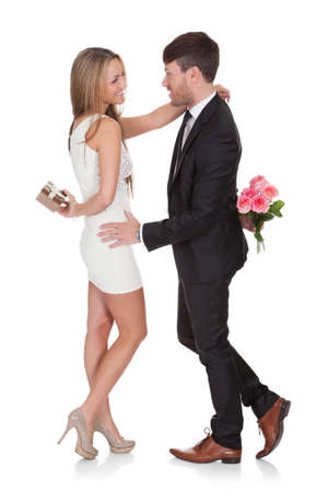 Man giving fresh flowers to woman. Isolated on white Stock Photo - 16522566