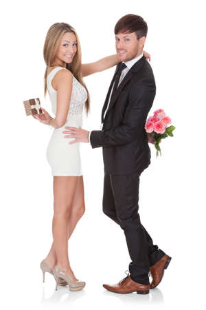 Man giving fresh flowers to woman. Isolated on white Stock Photo - 16522568