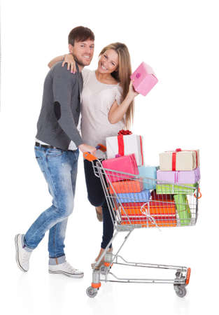 full shopping cart: Best friends shop valuable gifts for christmas presents. Isolated on white Stock Photo