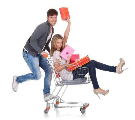 man pushing: Woman carried by push cart held by man.