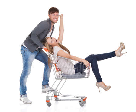 Handsome young man going out to shop pushing his carefree laughing wife along in a shopping trolley or cart as they have a fun day out photo