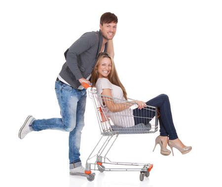 Handsome young man going out to shop pushing his carefree laughing wife along in a shopping trolley or cart as they have a fun day out Stock Photo - 16522686