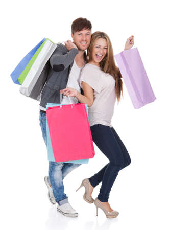 Guy and gal brings shopping bags in variety of colors. Stock Photo - 16522557