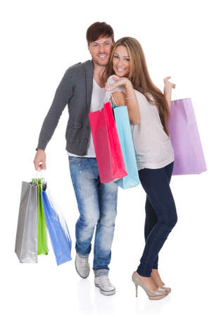 laden: Guy and gal brings shopping bags in variety of colors. Stock Photo
