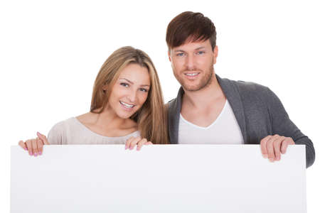Positive young couple with blank white board isolated on white photo