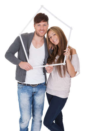 buying a house: Smiling attractive young couple posing standing close together on a white background