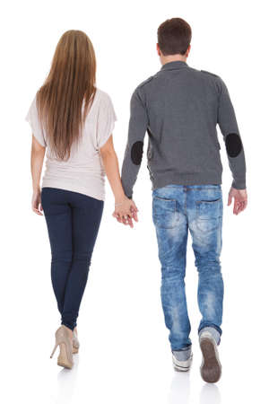 man rear view: Sweet partners hold each others hands while walking.
