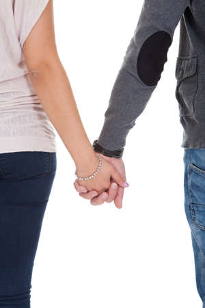 holding arm: Cropped rear view image of a man and woman in casual clothing holding hands isolated on white