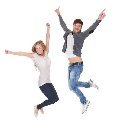 jubilation: Jubilant young man and woman leaping high in the air for joy with their arms raised isolated on white Stock Photo