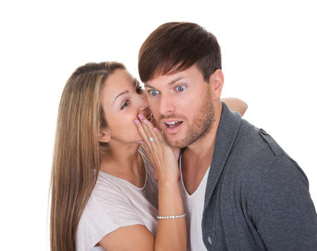 secretive: Young woman whispered something naughty in mans ear. Stock Photo