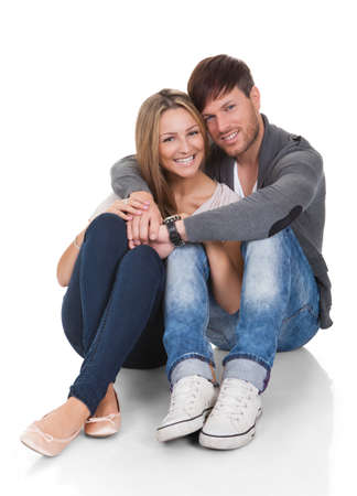 Young couple in love sitting close together on the floor in an affectionate embrace smiling at the camera Stock Photo - 16522066