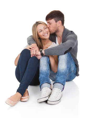 Young couple in love sitting close together on the floor in an affectionate embrace smiling at the camera Stock Photo - 16522143