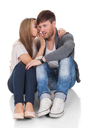 Young woman whispered something naughty in man's ear.