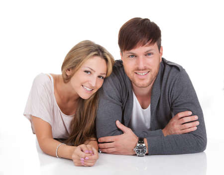 Happy young couple lying on white background Stock Photo - 16522204