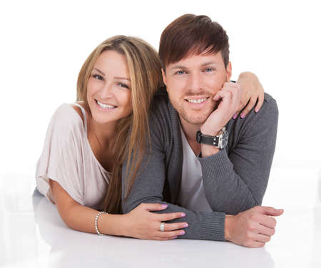 Happy young couple lying on white background