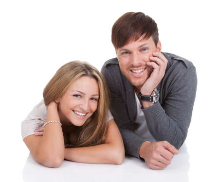 Happy young couple lying on white background Stock Photo - 16522241