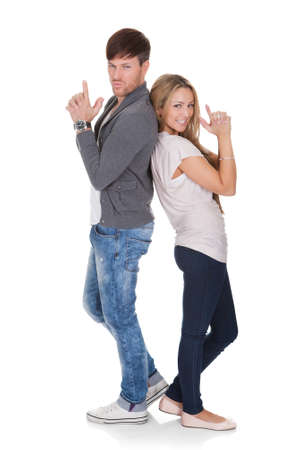 dueling: Fun image of a young attractive dueling couple standing back to back with their hands raised on a white background
