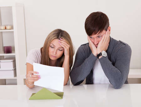 trouble: Shock portrayed on mans face after reading letter. Stock Photo