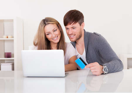 Couple shopping at online store paying via credit card. photo