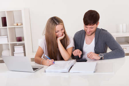 Young couple working on expenses at home photo