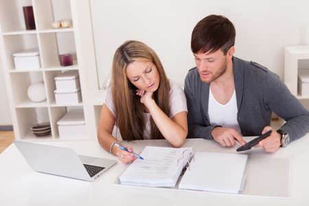 personal banking: Unhappy young couple in financial trouble at home