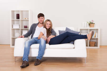 good looking man: Couple sit on new couch bought at furniture shop. Stock Photo