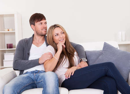 Cheerful young couple dreaming about the future sitting at couch Stock Photo - 16522009