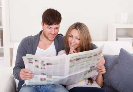 reading news: Both read recent article dealing relationships from newspaper. Stock Photo
