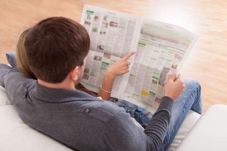 newspaper reading: Both read recent article dealing relationships from newspaper. Stock Photo