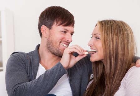 pareja comiendo: La alimentación del hombre joven barra de chocolate a su novia en casa