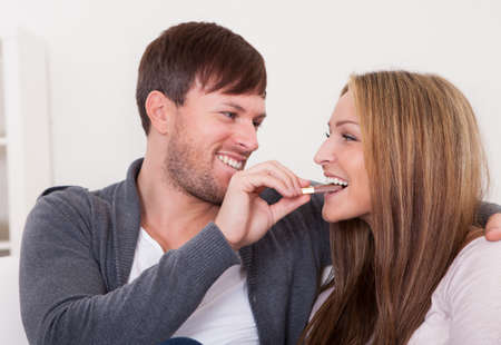 Young man feeding chocolate bar to his girlfriend at home Stock Photo - 16521949