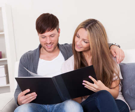 They look at family photo album in relative's house nearby. Stock Photo - 16522085