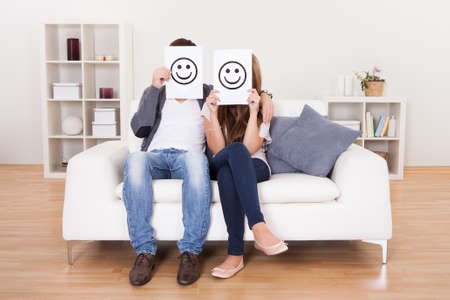 happiness symbol: Couple covered faces with smiley white paper. Stock Photo