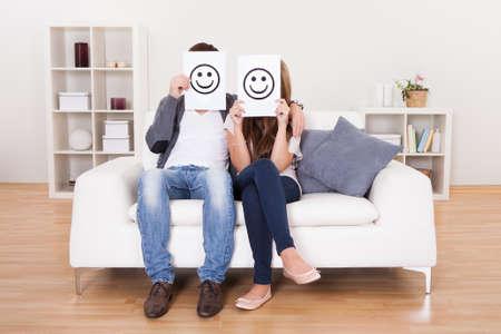 muebles de madera: Pareja cubierto caras sonrientes con papel blanco.