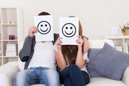 face covered: Couple covered faces with smiley white paper. Stock Photo
